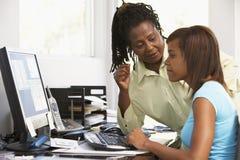 Frau und Tochter benutzen einen Computer Stockbild