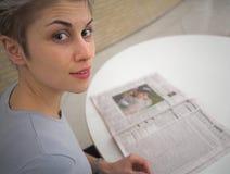 Frau und Zeitung Stockfotos