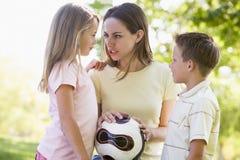 Frau und zwei junge Kinder, die Volleyball anhalten