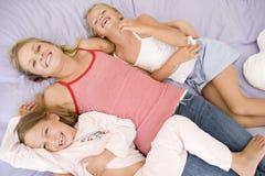Frau und zwei junge Mädchen, die beim Bettspielen liegen Lizenzfreie Stockbilder