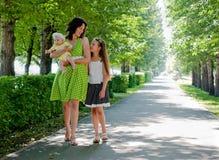 Frau und zwei Kinder, die hinunter die Allee gehen Lizenzfreie Stockfotografie