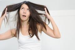 Frau unglücklich mit der Bedingung ihr langes Haar lizenzfreie stockbilder