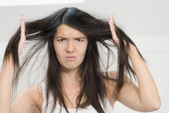 Frau unglücklich mit der Bedingung ihr langes Haar stockfotografie