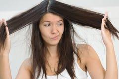 Frau unglücklich mit der Bedingung ihr langes Haar lizenzfreies stockbild