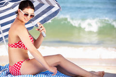 Frau unter dem Strand-Regenschirm, der auf Sun-Cr sich setzt Stockfotos