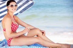 Frau unter dem Strand-Regenschirm, der auf Sun-Cr sich setzt Lizenzfreies Stockbild