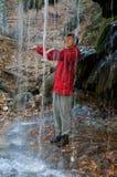 Frau unter dem Wasserfall Stockbild