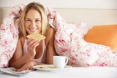 Frau unter Duvet Frühstück essend stockbild