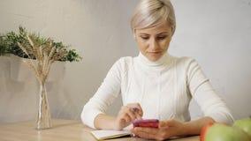 Frau unter Verwendung der zellulären und machenden kleinen Anmerkungen in ihrem Tagebuch stock footage
