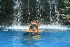 Frau unter Wasserfall. Stockbild