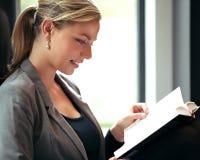 Frau untergetaucht in einem Buch Lizenzfreies Stockfoto