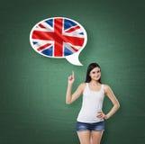Frau unterstreicht die Gedankenblase mit Großbritannien-Flagge Grüner Kreide-Brett-Hintergrund Lizenzfreie Stockbilder