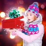 Frau untersucht den Weihnachtskasten mit magischen Lichtern Stockfotos