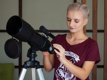 Frau untersucht durch ein Fenster ein Teleskop stockfoto