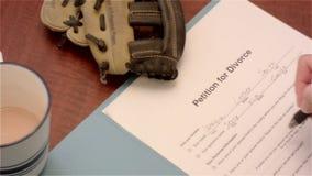 Frau unterzeichnet Scheidungspapiere und setzt Ehering auf sie stock footage
