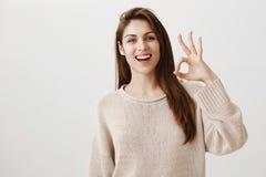 Frau vergewissert sich, dass alles fein geht Porträt des freundlichen sicherlich kaukasischen Mädchens, das positiv anhebend läch stockfoto