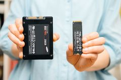 Frau vergleichen neue NVME-Antriebsscheibe mit SSD-Antriebsscheibe lizenzfreie stockbilder