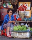 Frau verkauft Bananen auf Straßenmarkt in der Farbe, Vietnam Lizenzfreie Stockbilder