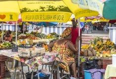 Frau verkauft frische Früchte am Markt im Freien in Guadeloupe Stockfoto