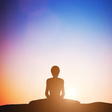 Frau in verklemmter Winkelyogahaltung meditierend bei Sonnenuntergang zen Lizenzfreies Stockfoto