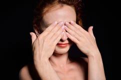 Frau versteckt mit ihren Händen Stockbilder