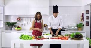 Frau versuchen, Bestandteile zur Salatschüssel zu verbreiten stock footage