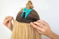 Frau versucht auf Haar-Erweiterungsclipn des blonden remy Clips natürlichen stockbild