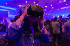 Frau versucht Kopfhörer der virtuellen Realität Lizenzfreie Stockfotos