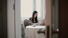Frau verwendet Laptop und das Genießen des Morgenkaffees auf einem hellen Speisen Ansicht durch die offenen Türen Lizenzfreie Stockfotografie