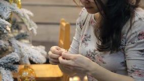 Frau verziert den Weihnachtsbaum und bindet Seil, um Spielwaren zu Hause zu hängen stock footage