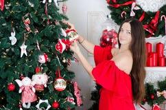 Frau verziert einen Weihnachtsbaum stockbilder