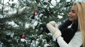 Frau verziert schneebedeckten Tannenbaum mit rotem Weihnachtsspielzeug draußen stock video