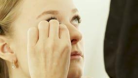 Frau visagiste unter Verwendung des Kosmetikschwammes für bilden junge Frau des Gesichtes im Schönheitsstudio Schließen Sie herau stock footage