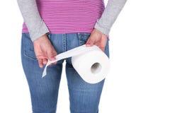 Frau von der Rückseite mit einer Toilettenpapierrolle Lizenzfreie Stockbilder