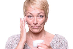 Frau von mittlerem Alter, die Antialterncreme aufträgt Lizenzfreie Stockbilder