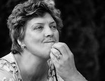 Frau von mittlerem Alter, die auf einem schwarzen Hintergrund aufwirft lizenzfreies stockbild