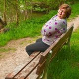 Frau von mittlerem Alter, die auf einer Parkbank sich entspannt Lizenzfreie Stockfotografie
