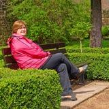 Frau von mittlerem Alter, die auf einer Parkbank sich entspannt Stockbild