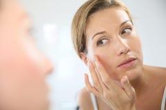 Frau von mittlerem Alter, die den Spiegel betrachtet und ihre Haut ernährt Stockfoto