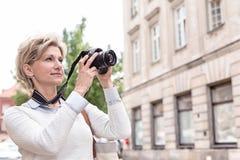 Frau von mittlerem Alter, die durch Digitalkamera in der Stadt fotografiert Stockbild