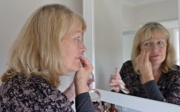 Frau von mittlerem Alter, die Gesichtspuder anwendet stockbilder