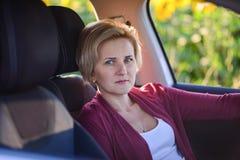 Frau von mittlerem Alter, die ihr Auto fährt Stockfotos