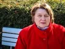 Frau von mittlerem Alter, die im Park auf einer Bank stillsteht lizenzfreie stockfotografie