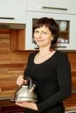 Frau von mittlerem Alter, die Kaffee zubereitet Lizenzfreies Stockfoto