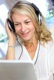 Frau von mittlerem Alter, die Kopfhörer verwendet Stockfotografie
