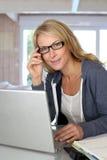 Frau von mittlerem Alter, die an Laptop arbeitet Lizenzfreie Stockbilder