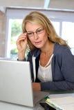 Frau von mittlerem Alter, die an Laptop arbeitet Lizenzfreies Stockbild