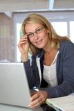 Frau von mittlerem Alter, die an Laptop arbeitet Stockbild