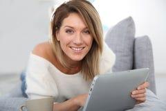 Frau von mittlerem Alter, die an Tablette arbeitet Stockbilder