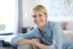 Frau von mittlerem Alter, die zu Hause auf Sofa sitzt Lizenzfreie Stockbilder
